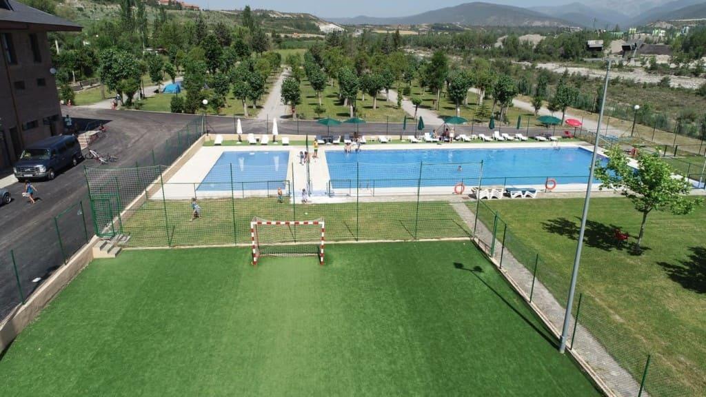 Vista aerea piscina, campo fútbol, chiringuito